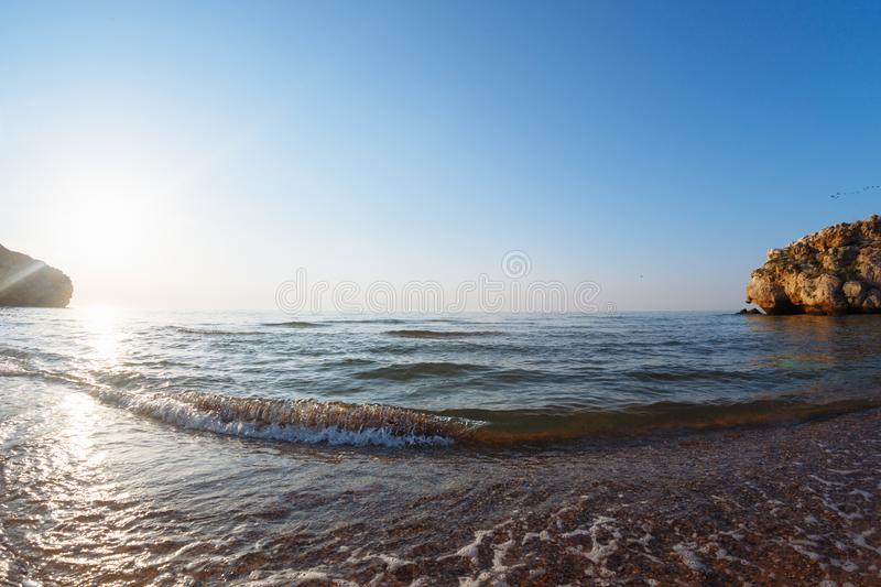 Sea with waves in a wild bay at sunset.  stock images