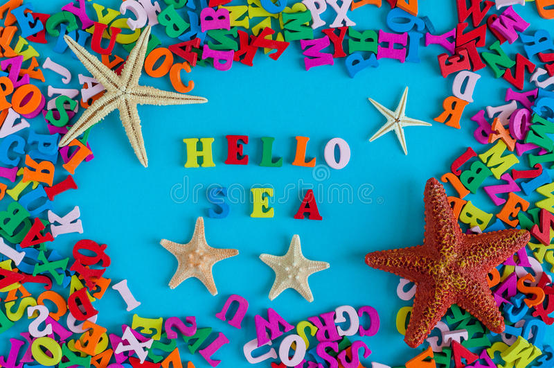 Sea - word composed of small colored letters. Starfish on a background of colourful turquoise blue table. Summer concept stock images