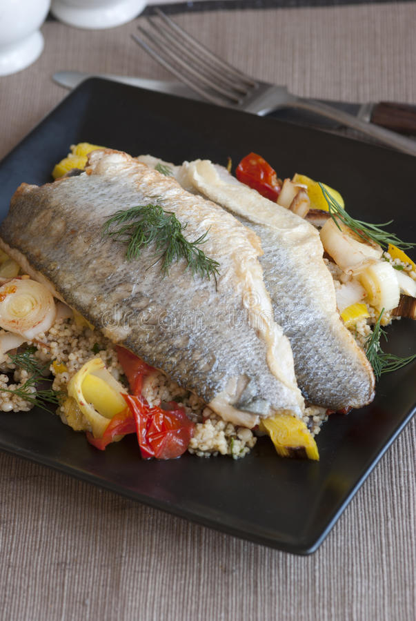 Seabass. Grilled seabass with couscous, vegetables and dill on a plate stock images