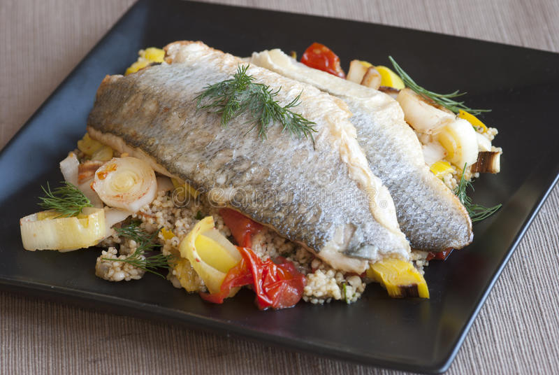 Seabass. Grilled seabass with couscous, vegetables and dill on a plate royalty free stock photography