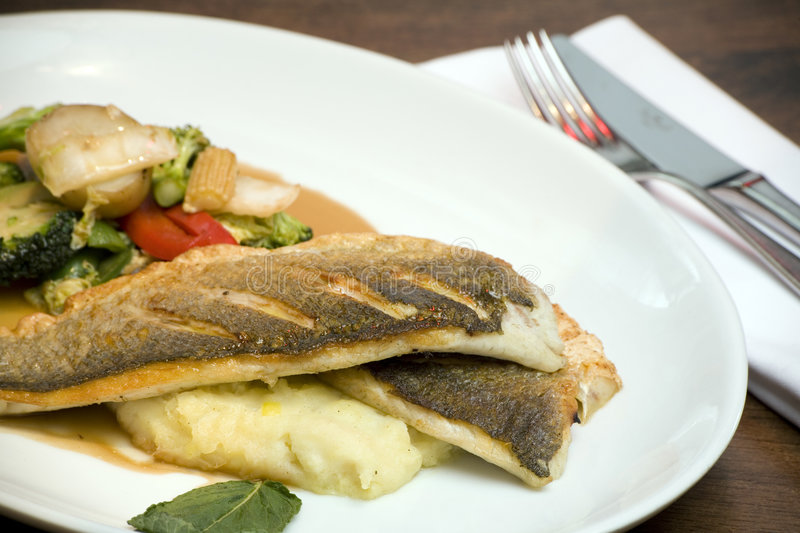 Seabass. A dish of grilled seabass with vegatables royalty free stock photos