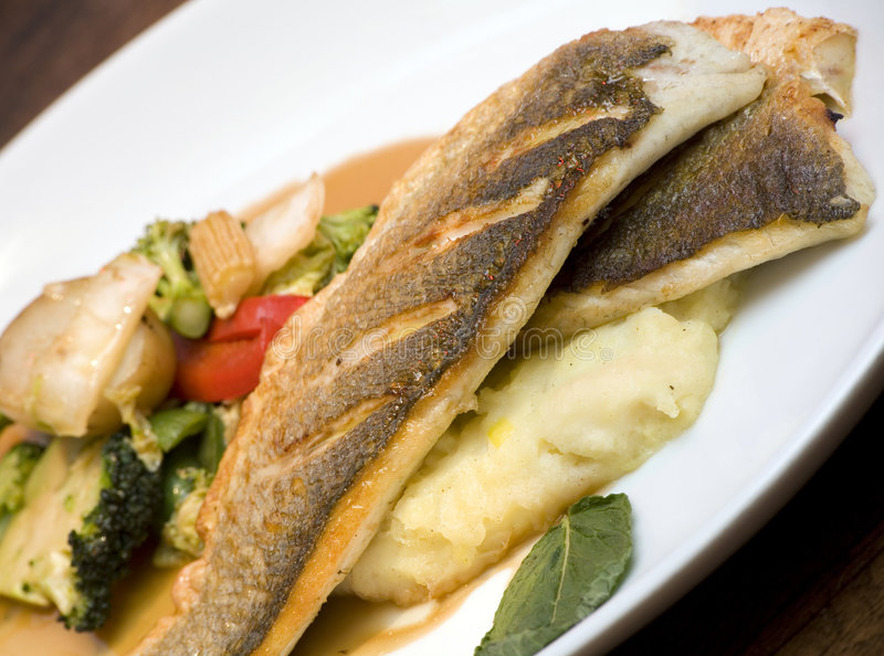 Seabass. A dish of grilled seabass with vegetables stock photos