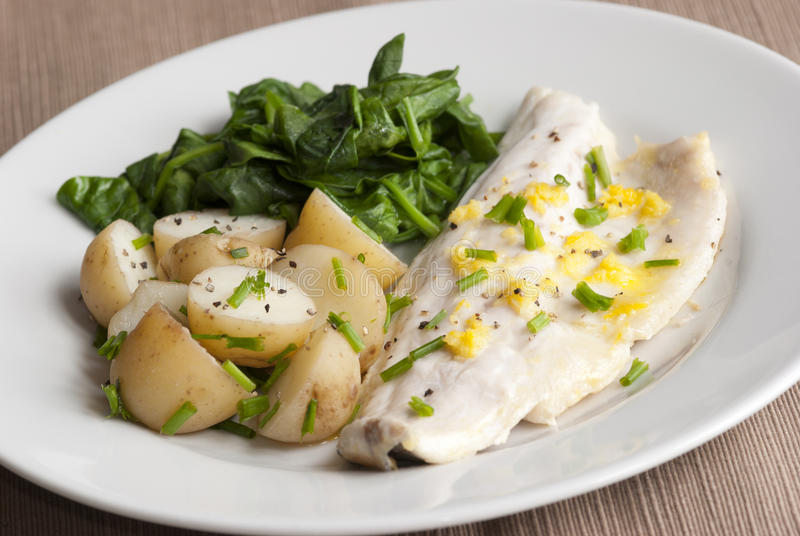 Seabass fillet. Delicious seabass with new potatoes and spinach on a plate royalty free stock image