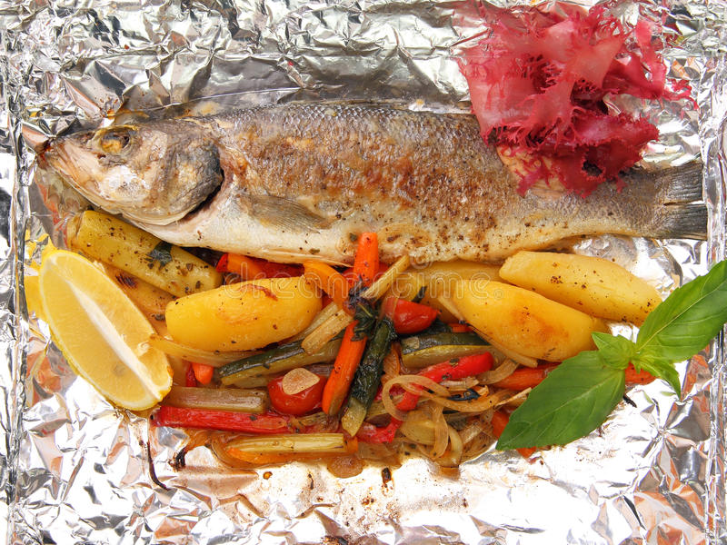 Seabass in foil. Seabass with vegetables baked in foil with ginger and twig of greens stock image