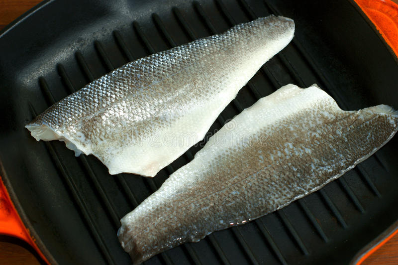 Seabass in a griddle pan stock images