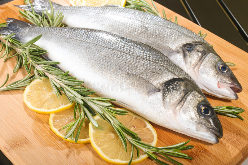 Seabass with lemon and rosemary. Two raw seabass with lime and rosemary on the wooden background royalty free stock image