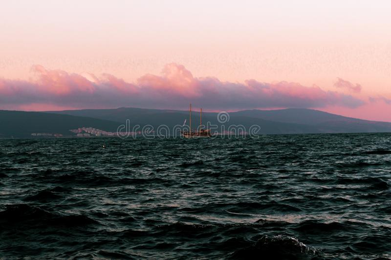 Seaboat on an ocean during sunset with beautiful evening clouds in the background stock photo