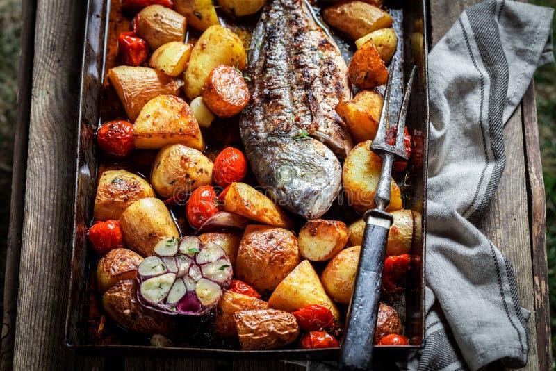 Seabream saboroso e batatas com os tomates de cereja na tabela escura fotos de stock royalty free