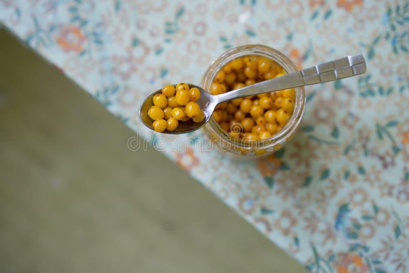 Seabuckthorn se mezcló con el primer de la miel en una cuchara encima de un tarro fotografía de archivo