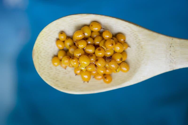 Seabuckthorn se mezcló con la miel en una cuchara de madera en un backgr azul fotografía de archivo libre de regalías