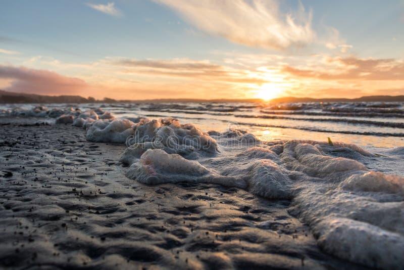Seafoam sur la plage pendant le beau coucher du soleil photo stock