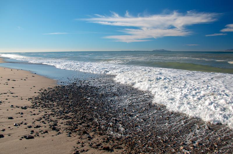 Seafoam waves washing over gravel on beach at McGrath State Park in Oxnard California USA. Seafoam waves washing over gravel on beach at McGrath State Park in royalty free stock photo