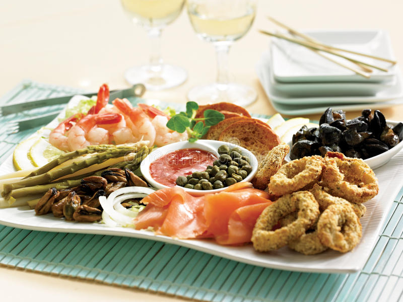 Seafood antipasto. Fish and seafood antipasto with cocktail sauce, capers and grilled bread. Two glasses of wine, chop sticks and a stack of plates in the stock photo
