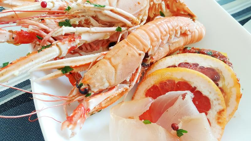 A seafood appetizer with prawn, tuna carpaccio and grapefruit slices stock photos