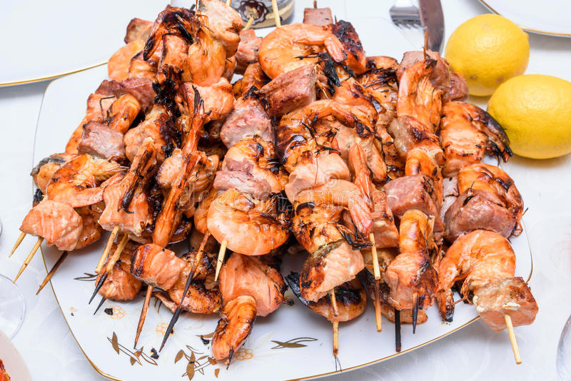 Seafood appetizers mix. Consisting of red salmon and tuna fish meat and shrimp on plate, close up stock images