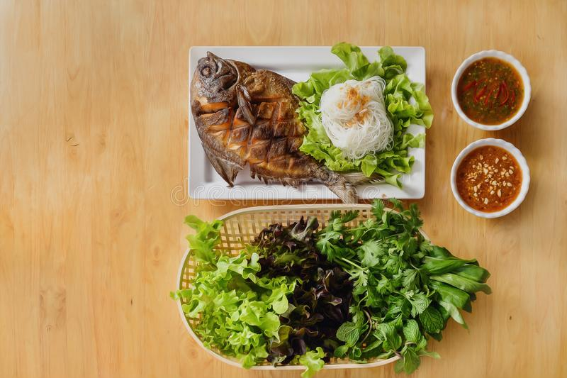 Seafood background of thai style deep fried butterfish with sweet and sour sauce served with rice noodel and vegetable stock photography