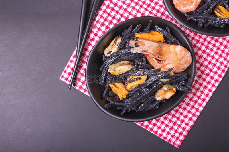 Seafood. Black homemade noodles of cuttlefish ink with mussels and shrimps. Asian cuisine.  royalty free stock photography