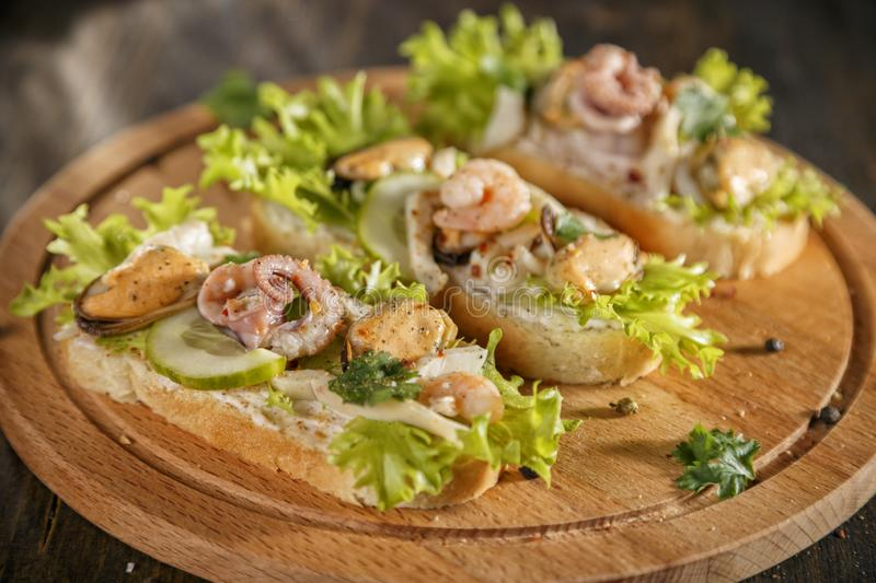 Seafood bruschetta topped with fresh salad, shrimp, octopus, mussel royalty free stock images