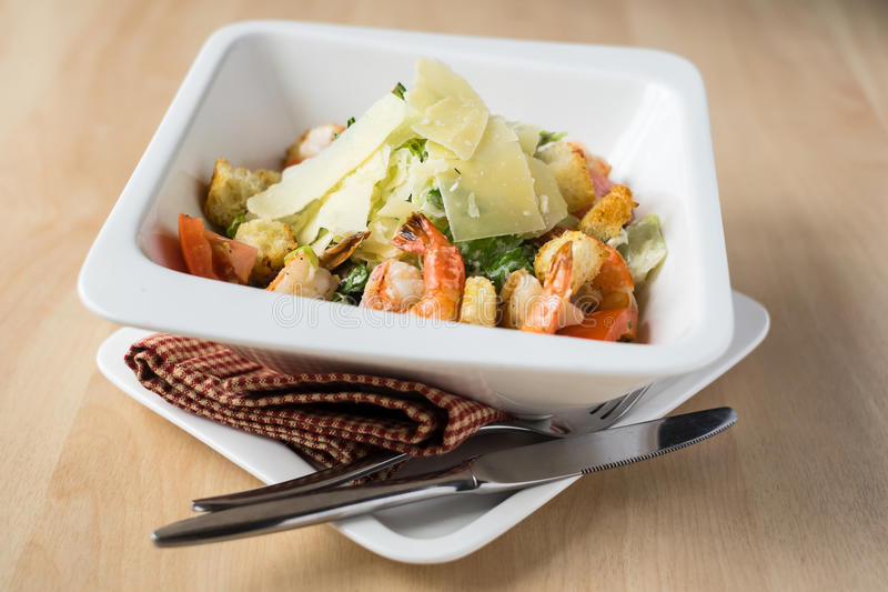 Seafood Caesar salad with shrimps, salad leaf, croutons, cherry tomato and parmesan cheese. In a plate, selective focus stock photography