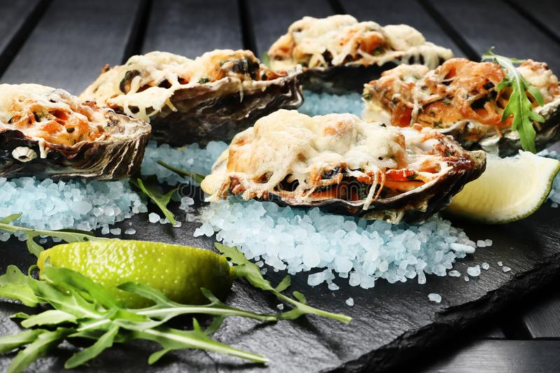 Seafood  with cheese and lime on a slate plate on black wooden  background. Seafood  with cheese and lime on a slate plate on black wooden background, sea stock images