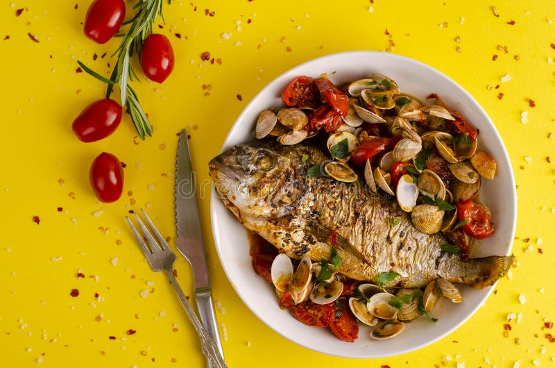 Seafood concept. Dorada with shellfish in tomato sause royalty free stock photos