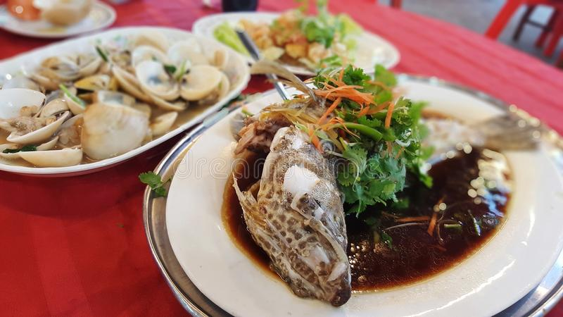 Seafood cooked chinese style. Steam fish seafood close-up ready to eat on red table dinner stock photography