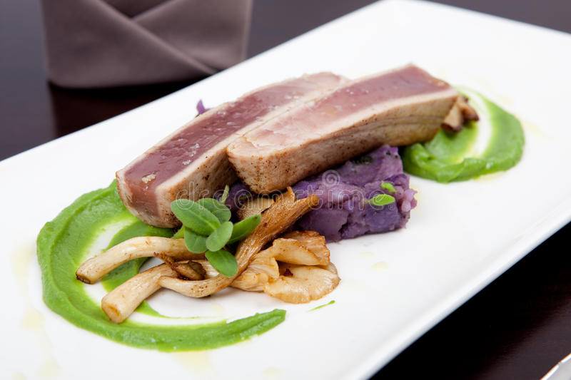 Seafood dinner with fillet of tuna, oyster mushrooms and pea puree. Delicious seafood dinner with fillet of tuna, green pea puree, oyster mushrooms and potatoes stock photography