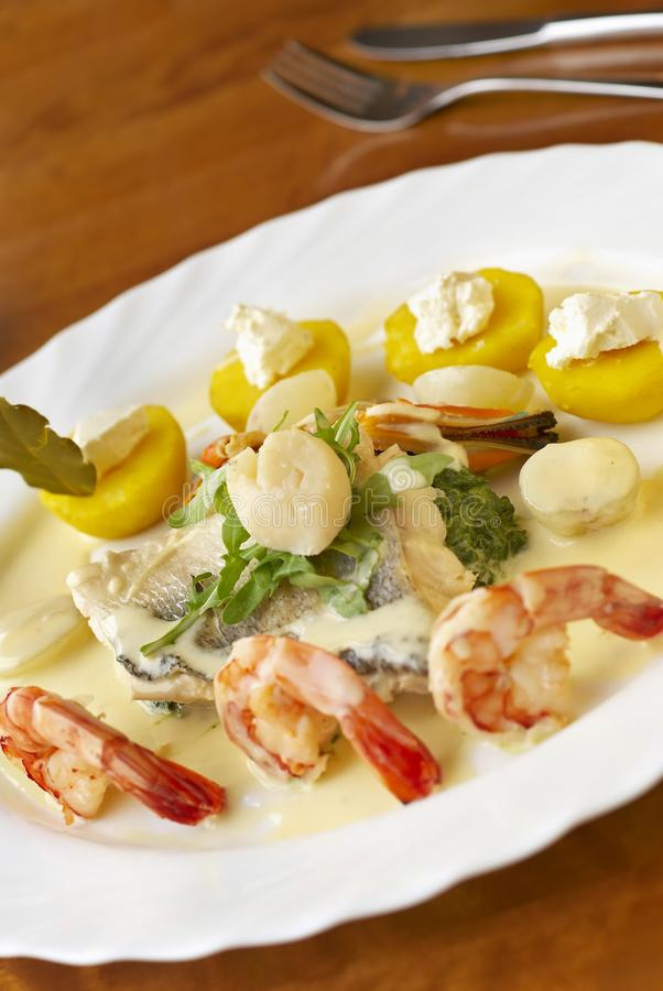 Seafood dish with spinach, potatoes and cream sauce royalty free stock photos