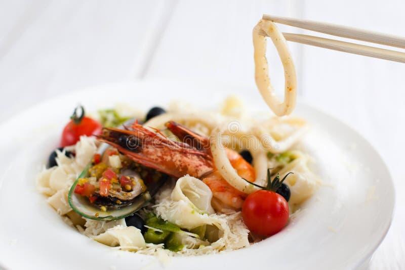 Seafood eating with chopsticks, closeup stock image