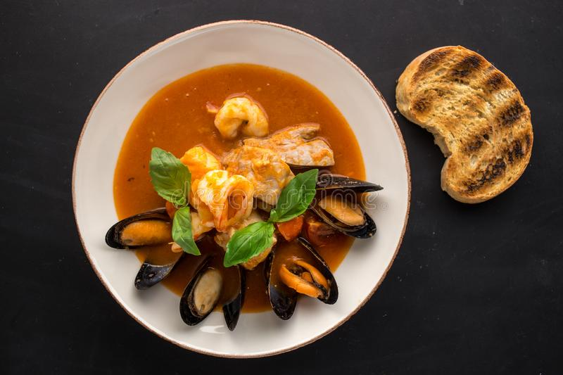Seafood fish soup with mussel and shrimps and piece of grilled bread on black background royalty free stock image
