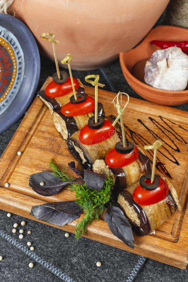 Seafood, Mediterranean cuisine, meat rolls with eggplant, cherry tomatoes, olives and greens on skewers. Caucasian national cuisine according to Georgian royalty free stock photography