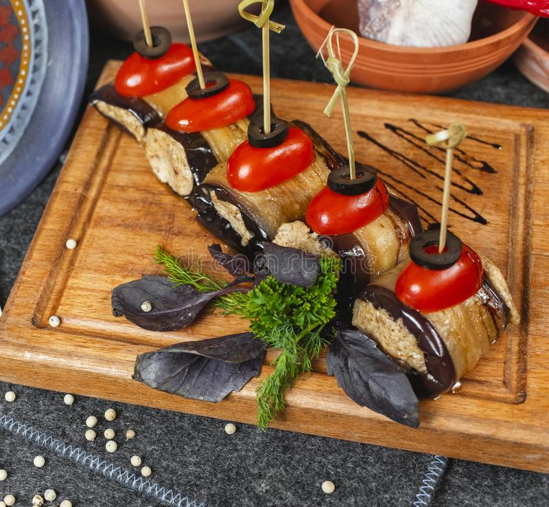 Seafood, Mediterranean cuisine, meat rolls with eggplant, cherry tomatoes, olives and greens on skewers. stock image