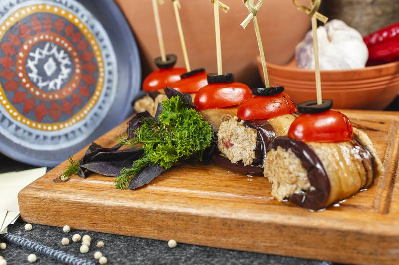 Seafood, Mediterranean cuisine, meat rolls with eggplant, cherry tomatoes, olives and greens on skewers. Caucasian national cuisine according to Georgian stock image