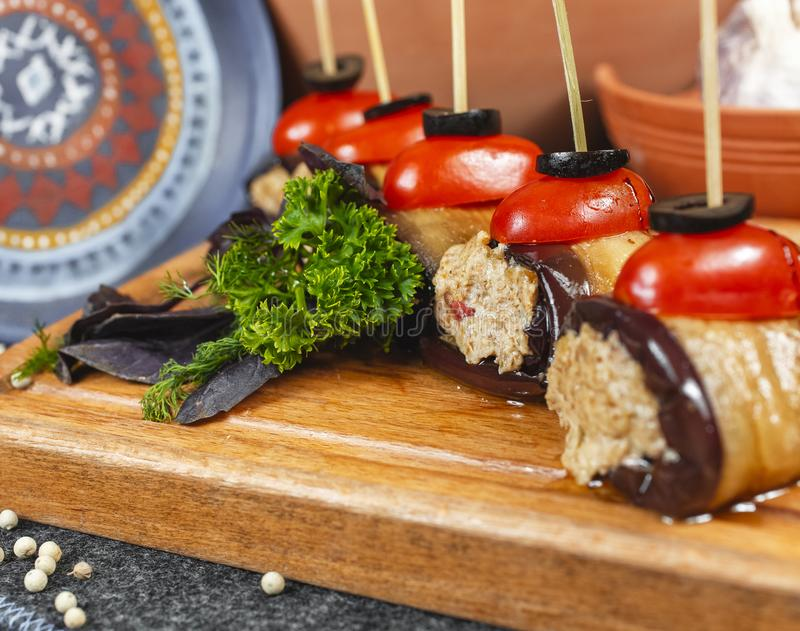 Seafood, Mediterranean cuisine, meat rolls with eggplant, cherry tomatoes, olives and greens on skewers. Caucasian national cuisine according to Georgian stock images