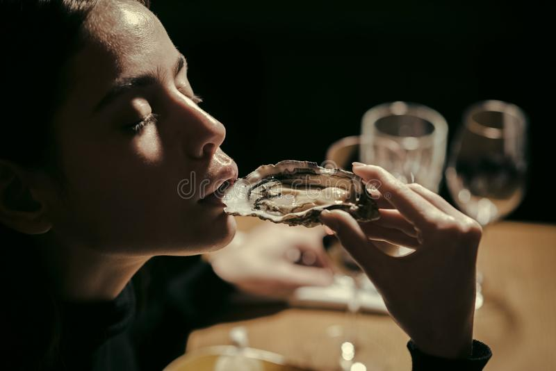 Seafood and Mediterranean cuisine with mussels in shell. Young woman eating oyster in luxury restaurant. Dieting and. Health stock image