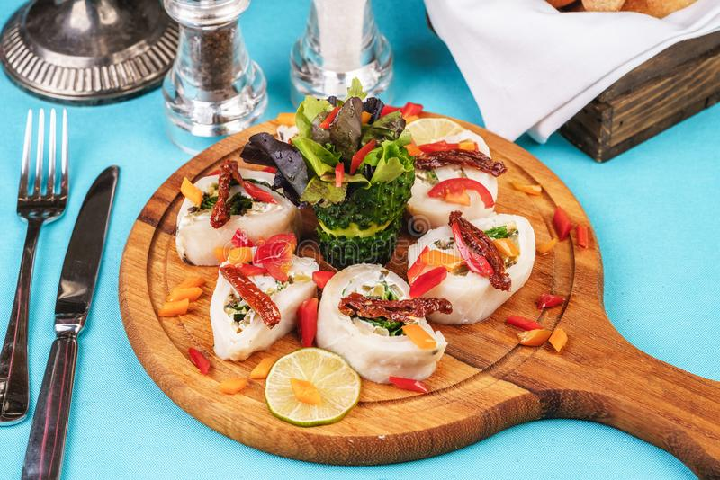 Seafood, Mediterranean cuisine. Vegetable rolls from sea fish with greens, cucumber, lemon and chili. Japanese food. Mediterranean cuisine, European dish stock photos