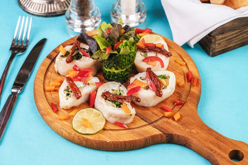 Seafood, Mediterranean cuisine. Vegetable rolls from sea fish with greens, cucumber, lemon and chili. Japanese food. Mediterranean cuisine, European dish stock images
