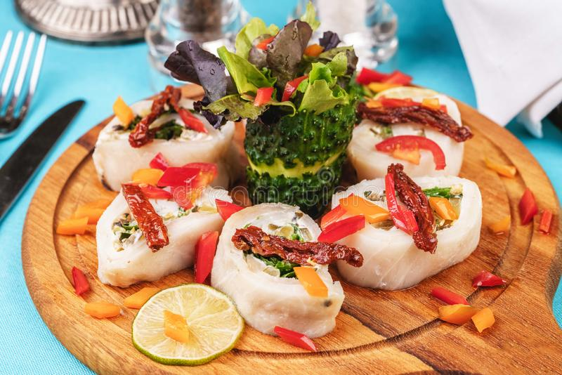 Seafood, Mediterranean cuisine. Vegetable rolls from sea fish with greens, cucumber, lemon and chili. Japanese food. Mediterranean cuisine, European dish royalty free stock image