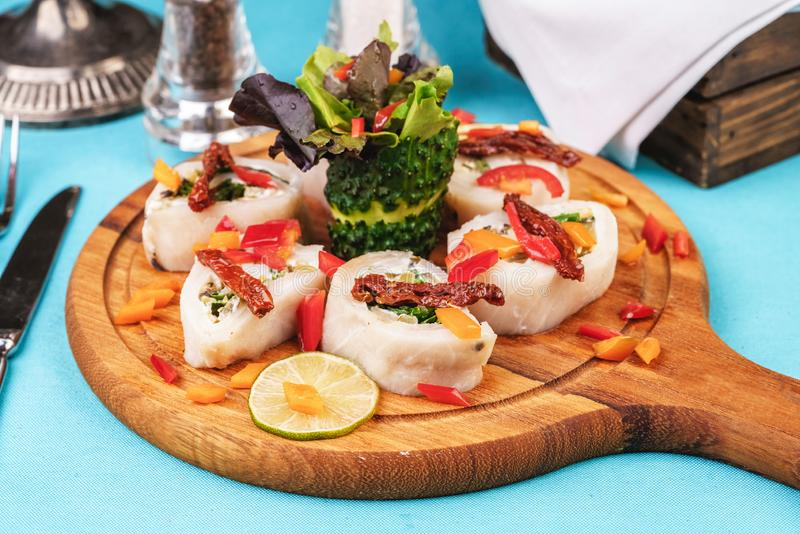 Seafood, Mediterranean cuisine. Vegetable rolls from sea fish with greens, cucumber, lemon and chili. Japanese food. Mediterranean cuisine, European dish stock image