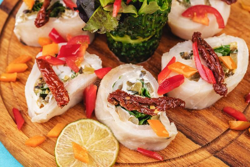 Seafood, Mediterranean cuisine. Vegetable rolls from sea fish with greens, cucumber, lemon and chili. Japanese food. Mediterranean cuisine, European dish stock photography
