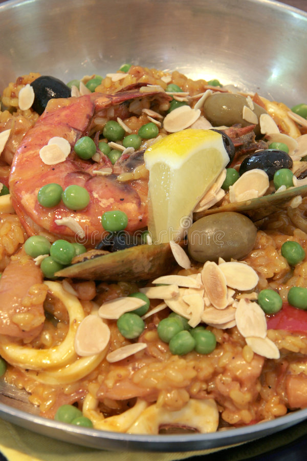 Seafood Paella. Rich seafood paella with baked almond slices and whole olives royalty free stock photography