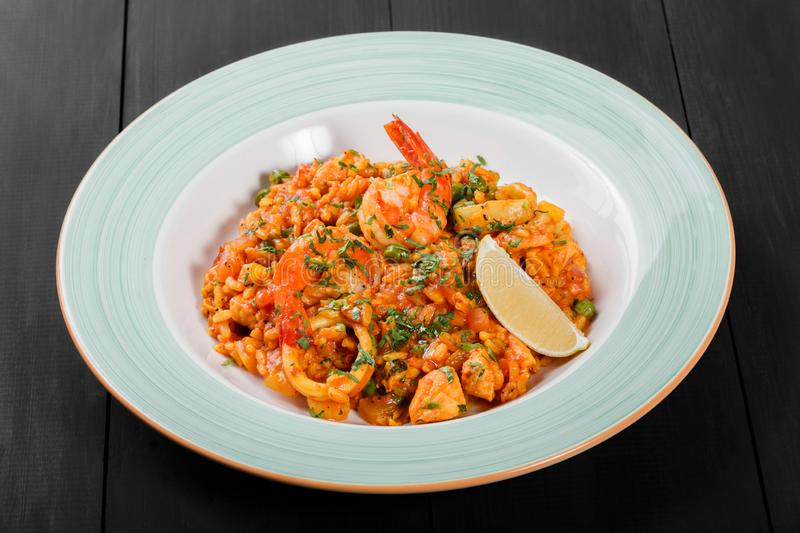 Seafood paella with rice, tomato sauce, langoustine, mussels, squid, shrimp and greens stock photos