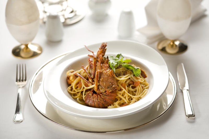 Seafood and pasta. Lobster with spaghetti pasta on white plate stock image