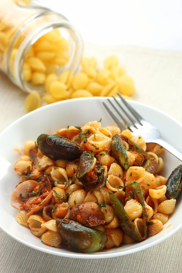 Seafood pasta in bowl. With raw pasta in background royalty free stock image