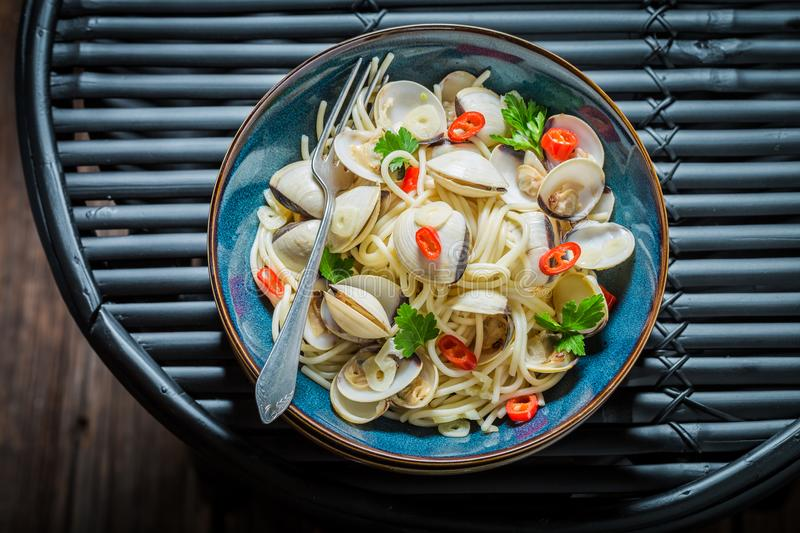 Seafood pasta with clams, parsley and peppers on black table royalty free stock photography