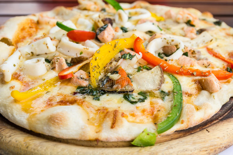 Seafood pizza. Closeup delicious pizza with seafood on wooden stand royalty free stock photo