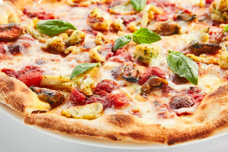Seafood pizza delicious. Seafood pizza closeup. Sliced traditional Italian cuisine with squid and mussel meat. Pizzeria restaurant dish isolated on white stock photo