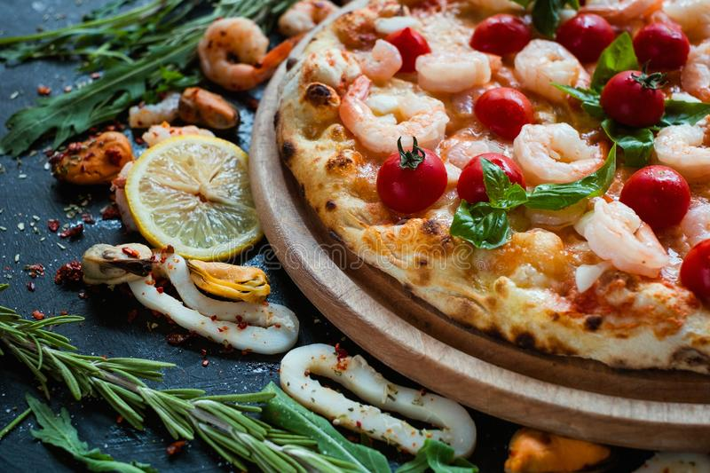 Seafood pizza tomato shrimp mediterranean food. Seafood pizza with shrimps and tomatoes. Tasty mediterranean style food concept stock image