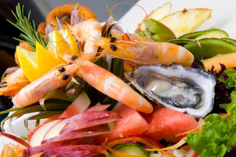 Seafood platter. Served fresh and deep fried surrounded with salad and fruit royalty free stock photography