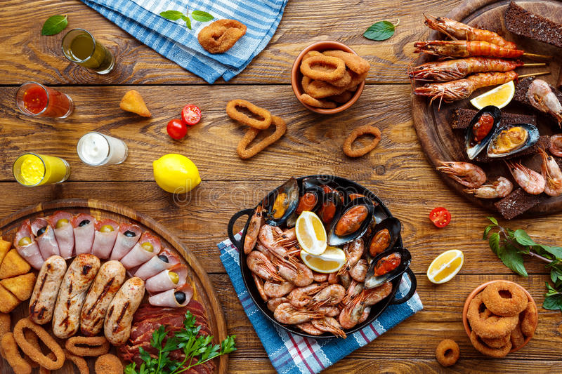 Seafood platter top view, flat lay on wooden table background. Seafood platter top view, flat lay. Mediterranean cuisine restaurant food, fried calamari rings royalty free stock photo